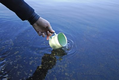 A hand dips a mug into a lake.