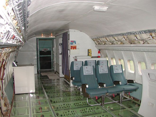 Interior of airplane home with some original seats and a washing machine