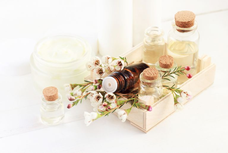 Natural perfumes in a wood tray on a white background with creams.