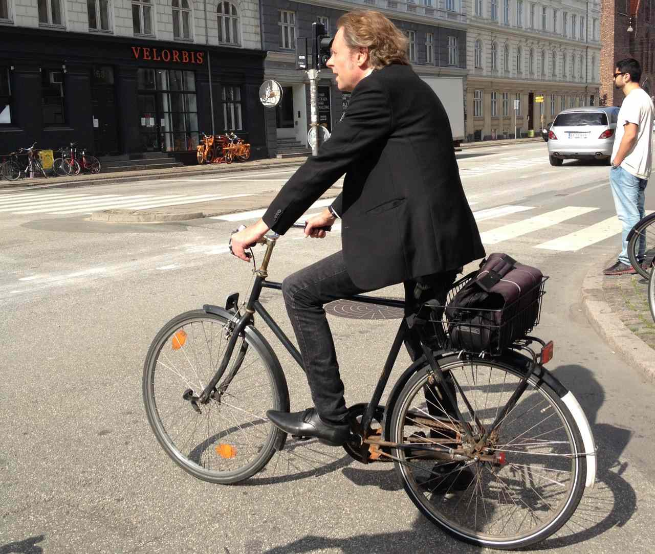 A man in a suit riding a bike on a city street
