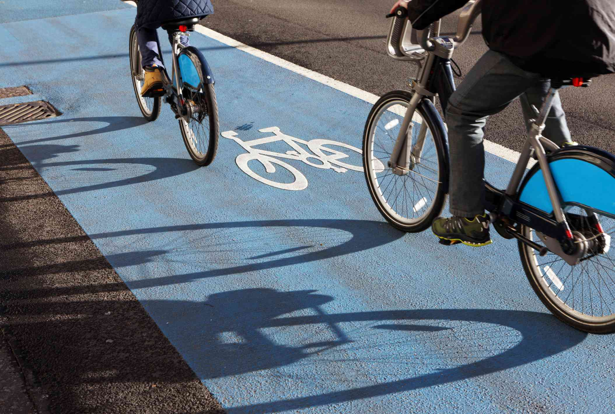 two cyclists riding on a marked blue bike lane on the London cycle superhighway