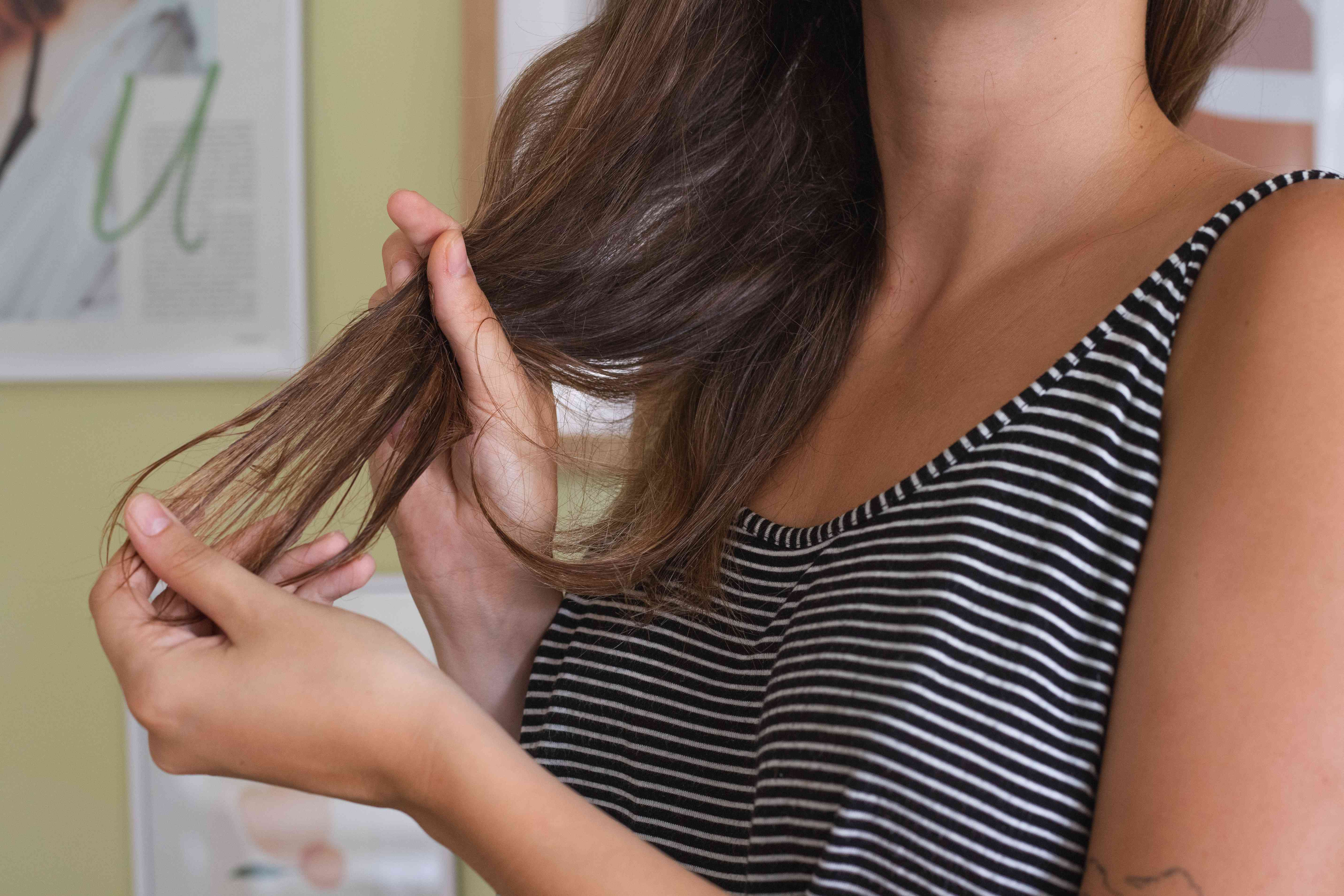 woman in striped tank rubs coconut oil onto the ends of brown hair