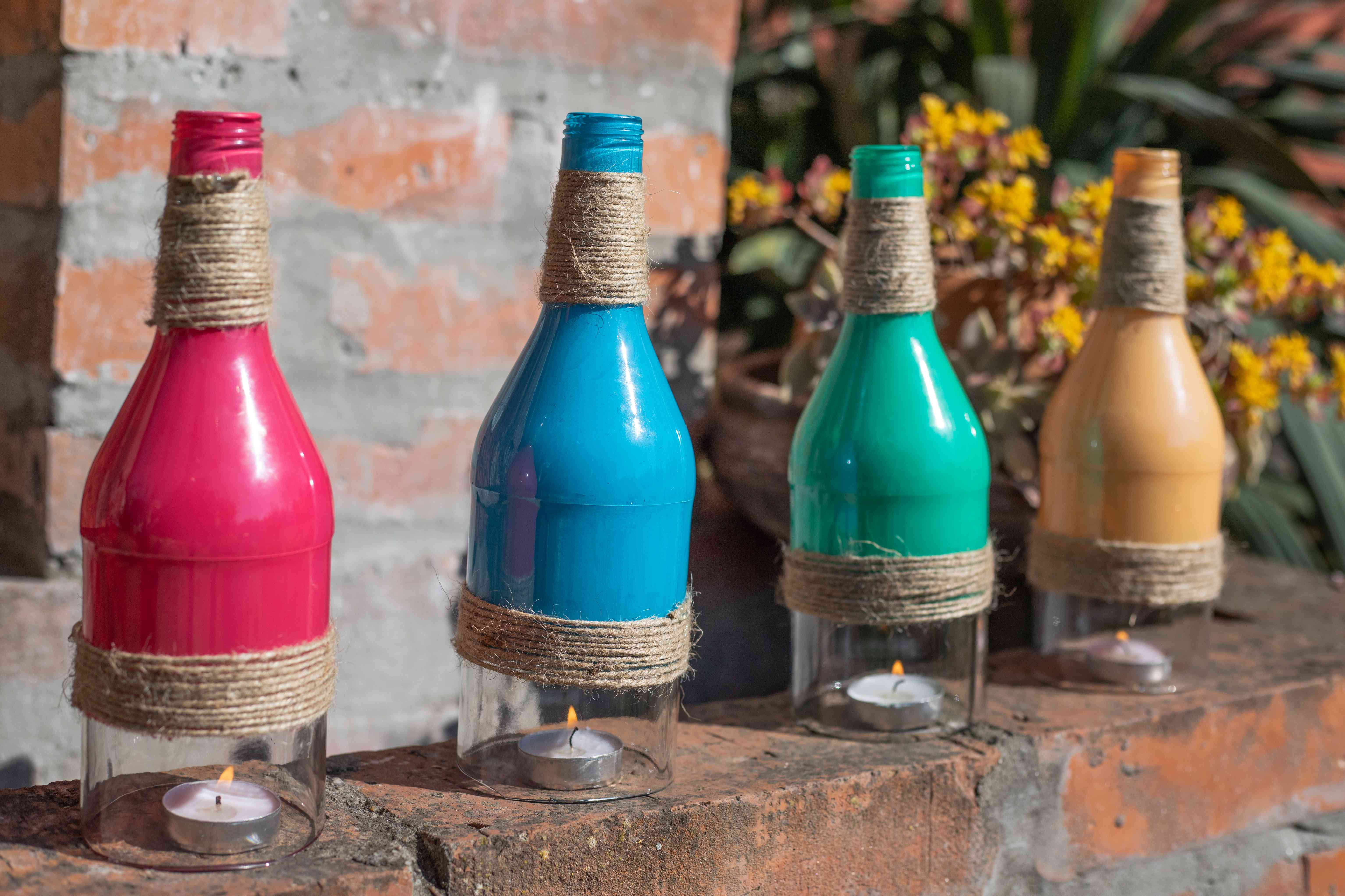 wine bottles painted and upcycled with twine placed over tea lights as outdoor lanterns