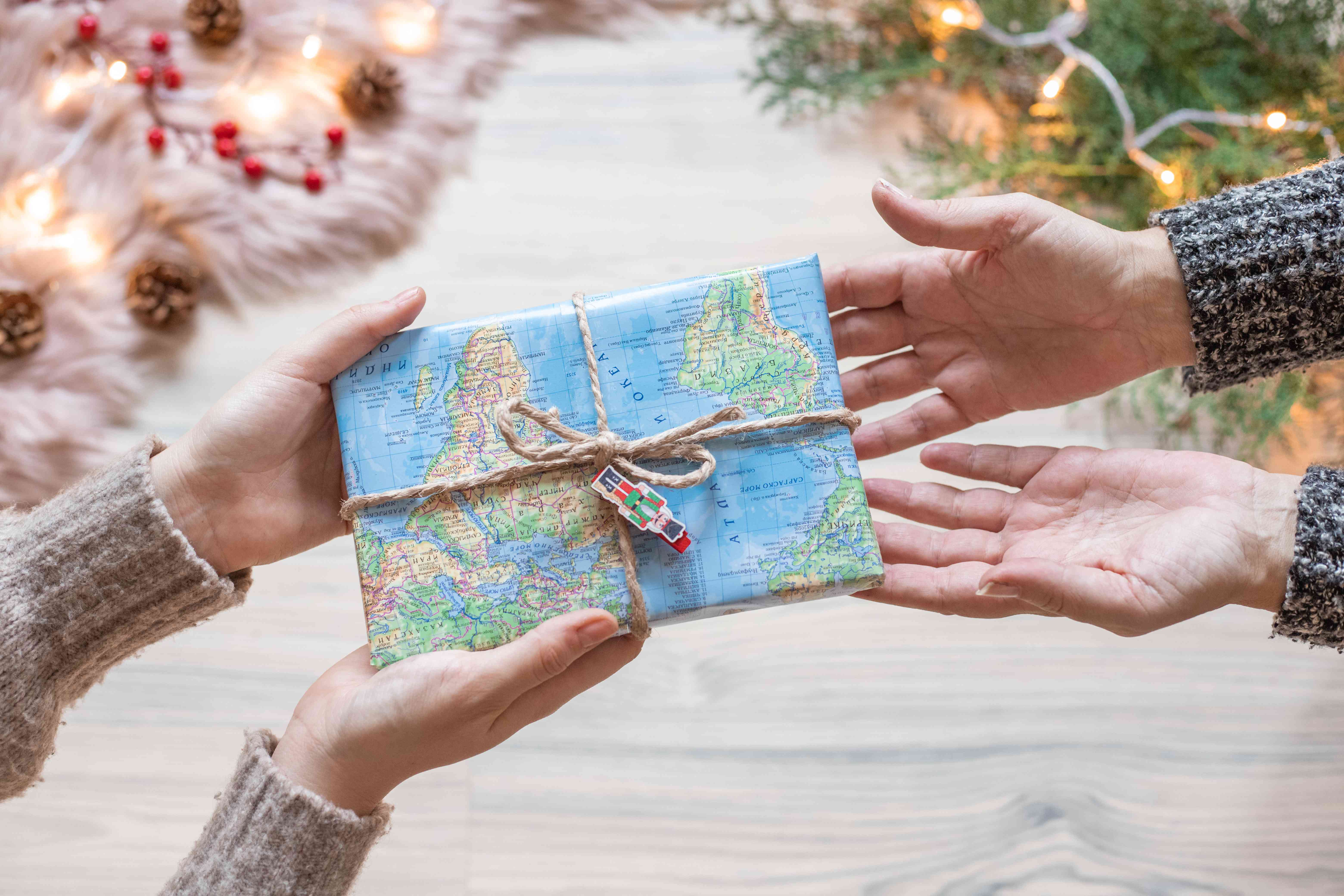 two friends exchange presents with map wrapping paper