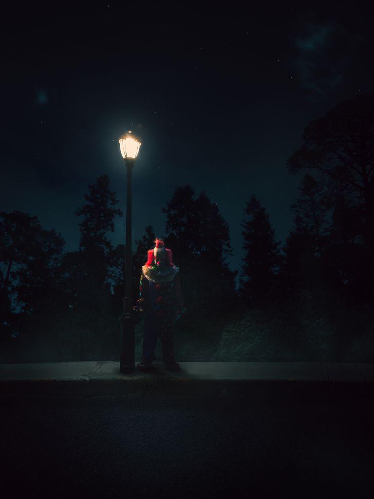 A clown standing on a street corner holding balloons