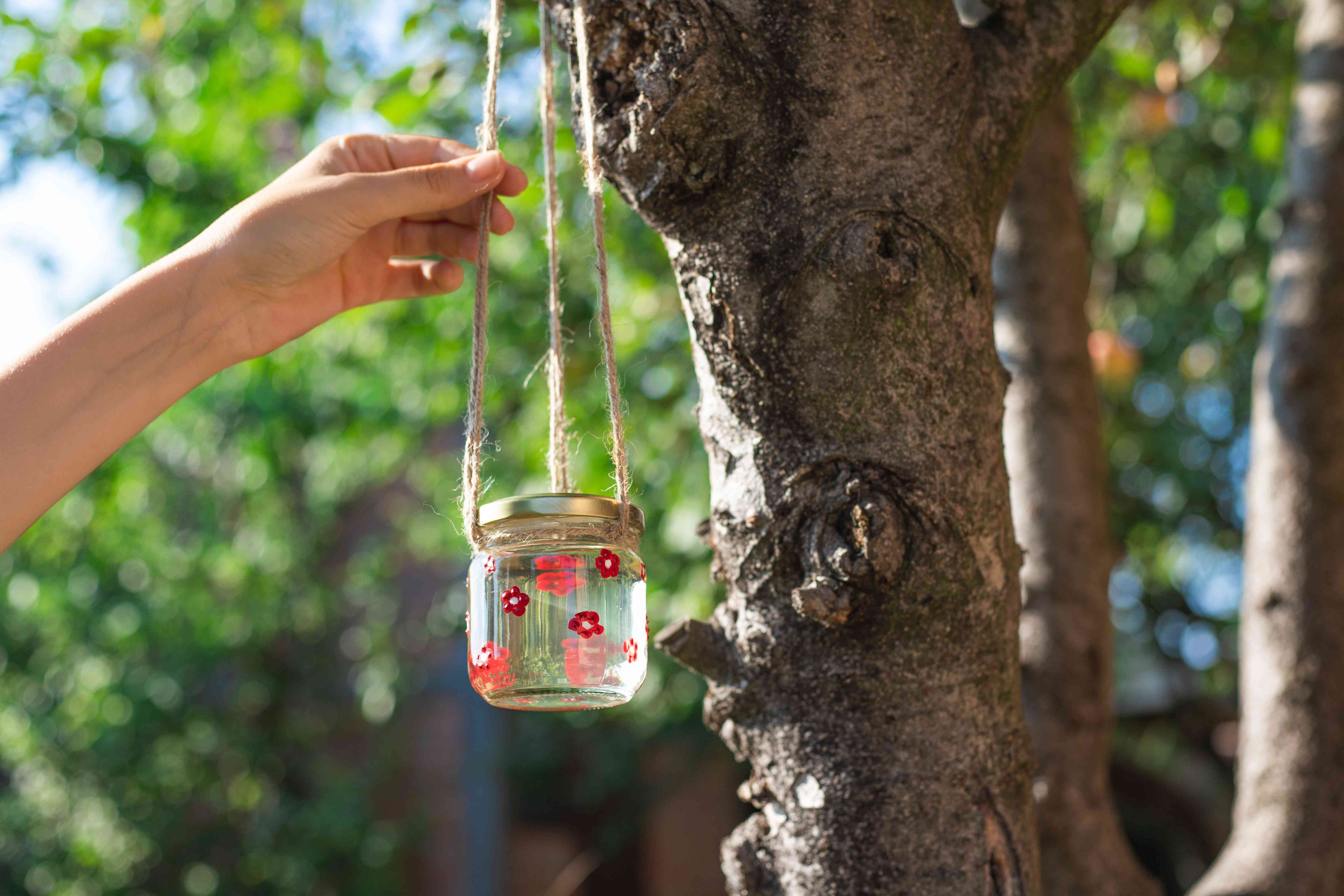 hands hang up diy hummingbird feeder with twine on tree outside