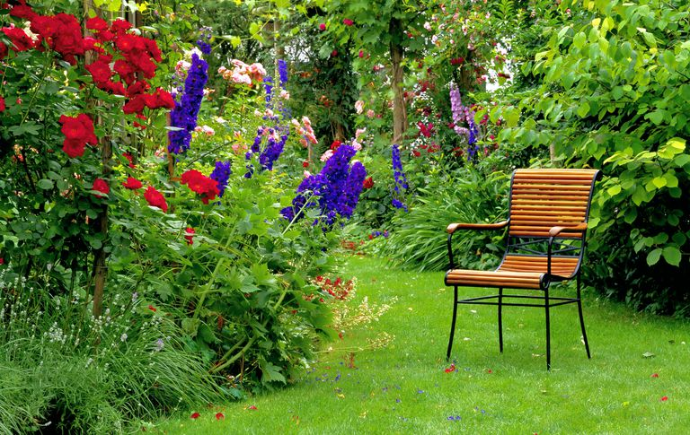 A chair sitting in a summer garden with red roses and other bushes and flowers.