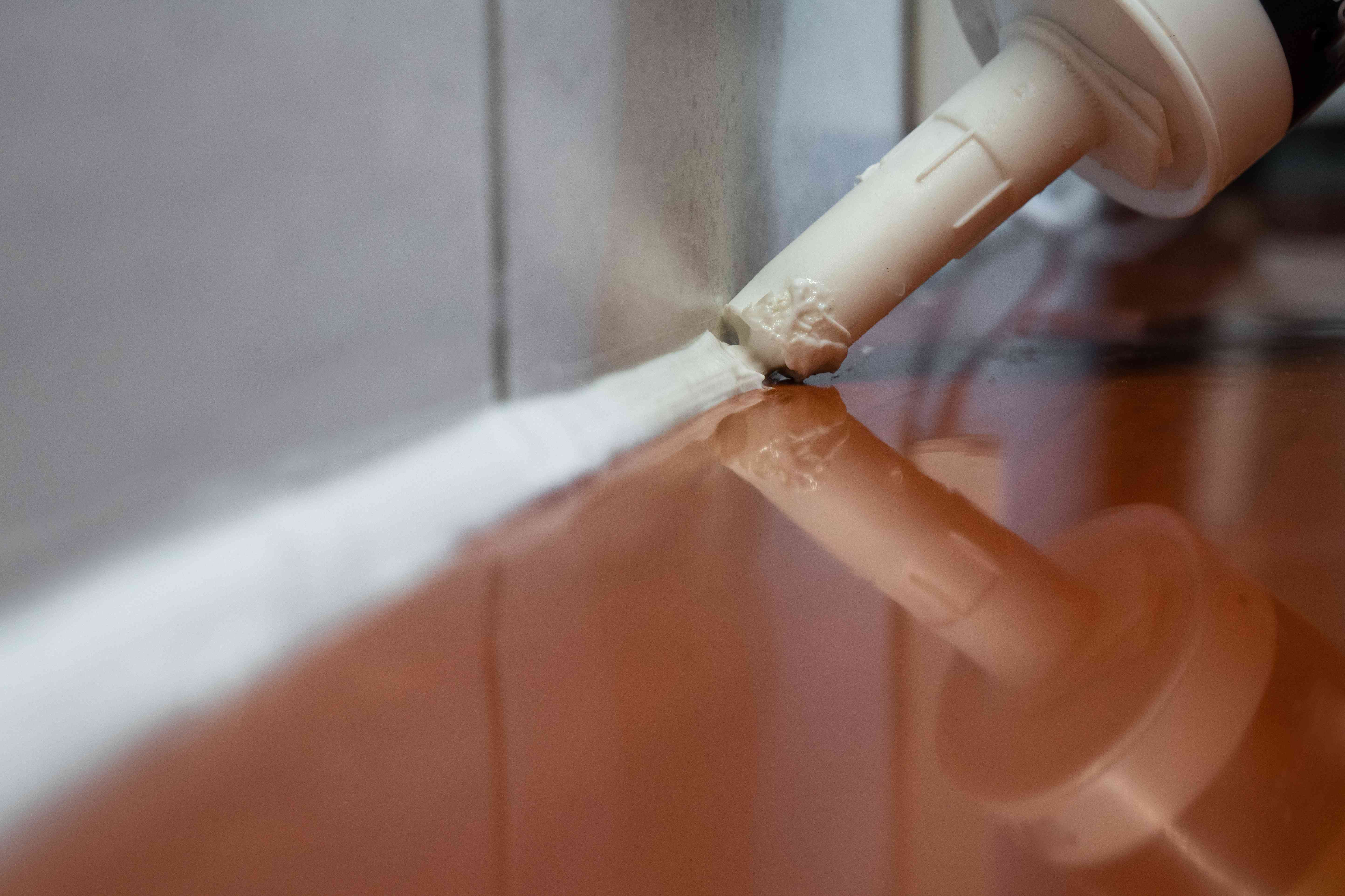 macro close up shot of caulking gun being squeezed in cracks of tile grout
