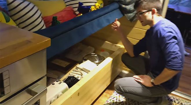A man crouches next to a pull-out wood drawer