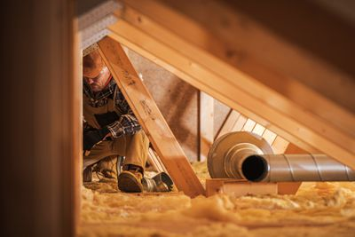 A man working on installing insulation in an attic.