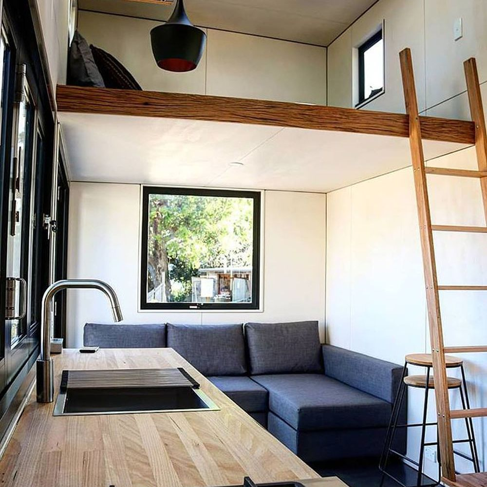 Living space with ladder going up to the bedroom loft