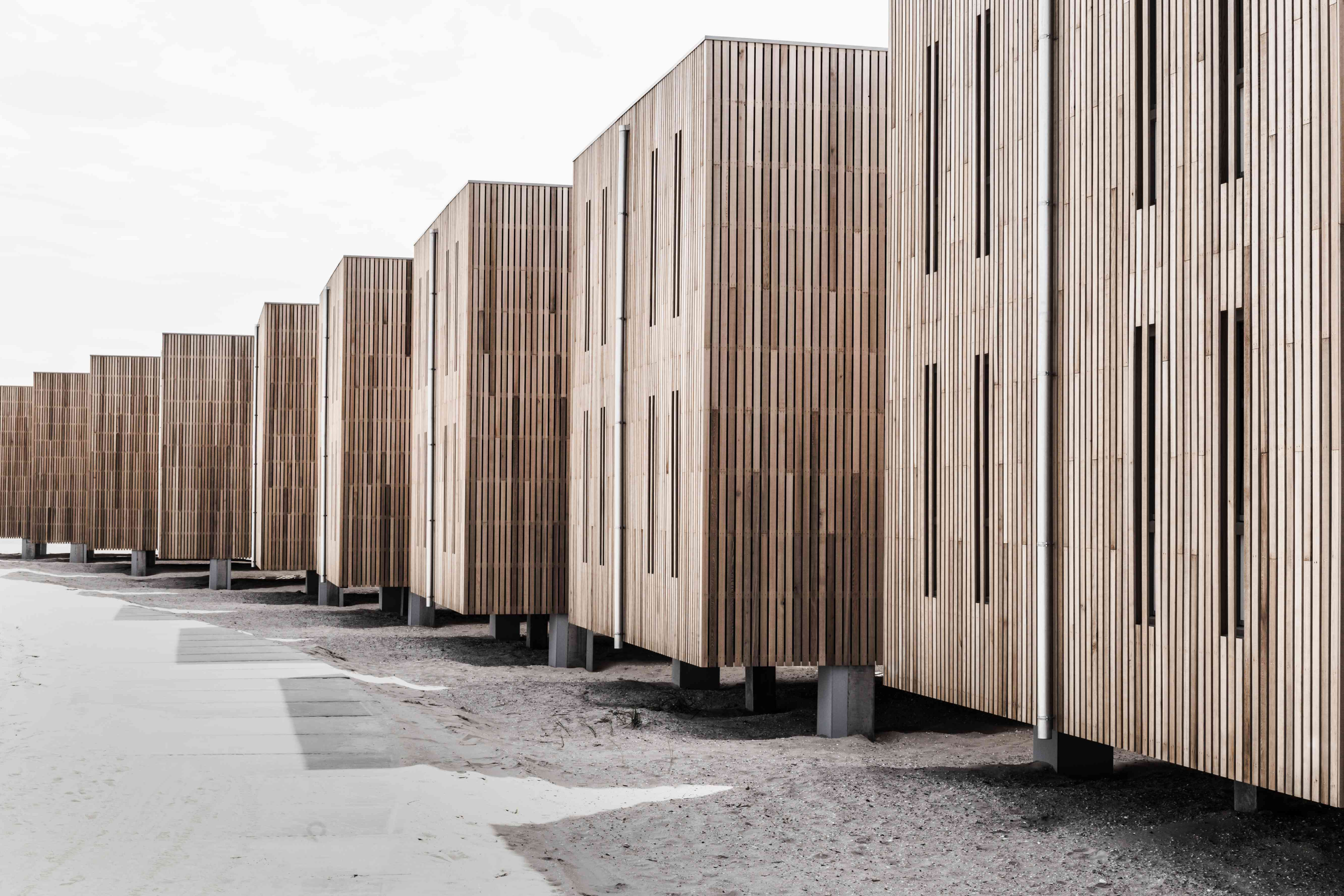 A rows of wooden buildings on the beach.