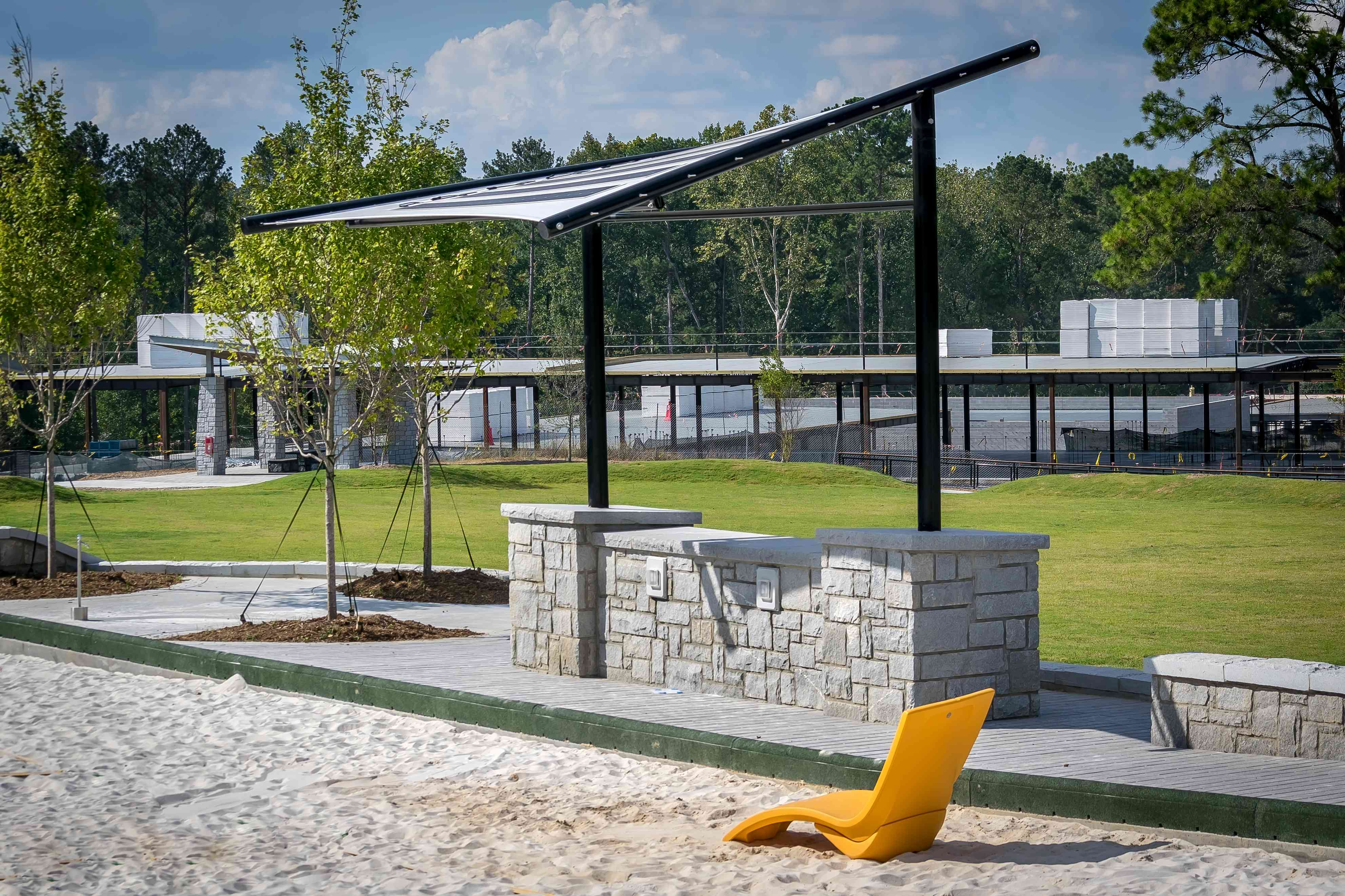 A solar panel in a park with a yellow lounge chair in the foreground.
