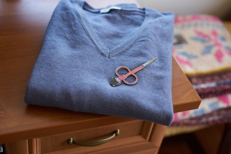 folded blue v-neck sweater on desk with small fabric scissors on top