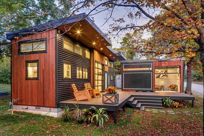 Exterior of tiny home in autumn showing both structures and the connecting deck