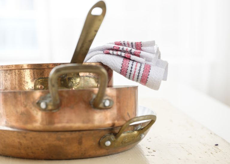 3 copper pans in a stack with a towel
