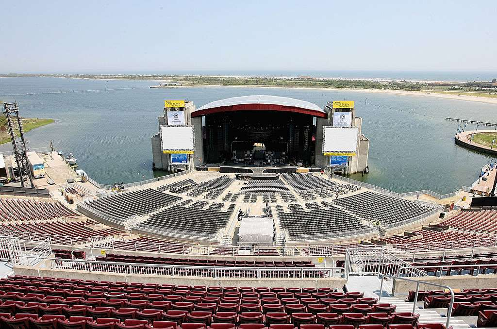 Aerial view of Nikon at Jones Beach Theater with water and a blue sky behind the stage from the back of the seating area