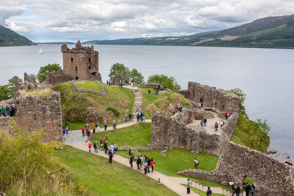 Tourists visiting castle ruins on the edge of Loch Ness