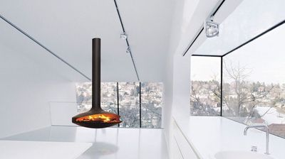 Free hovering fireplace in a white and glass room