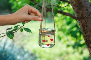 hand touches hanging twine attached to glass jar filled with diy hummingbird nectar