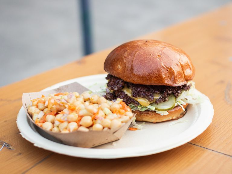 Burger and chickpea side dish on a compostable plate
