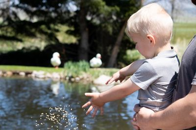 toddler boy throws duck food into pond with birds watching in background