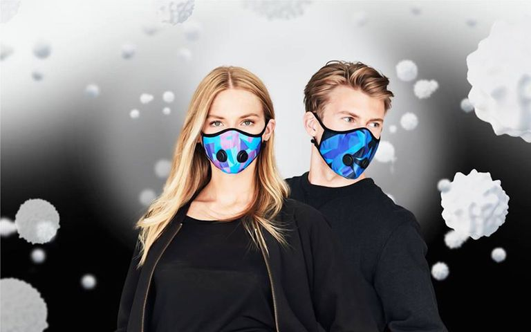A man and a woman both wearing multicolored face masks with valves