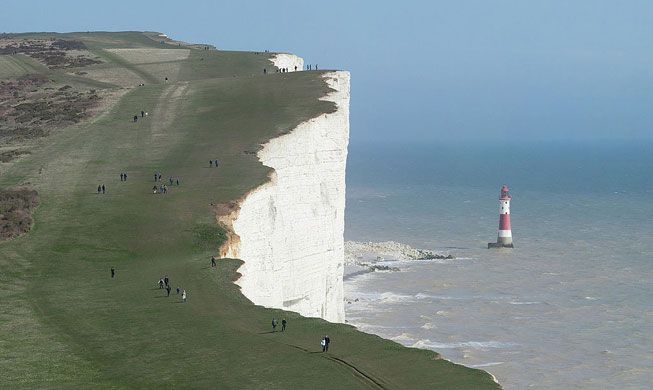 Hikers walk along the grassy cliffs of Beachy Head in East Sussex
