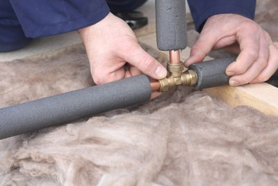 Plumber working on insulated copper pipes