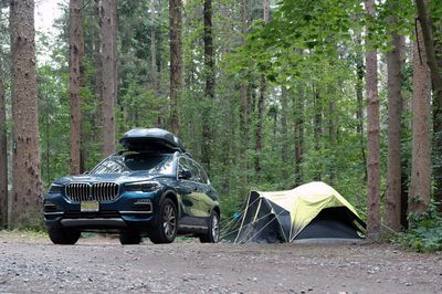 SUV with kayak on top and pitched tent nearby in camping ground