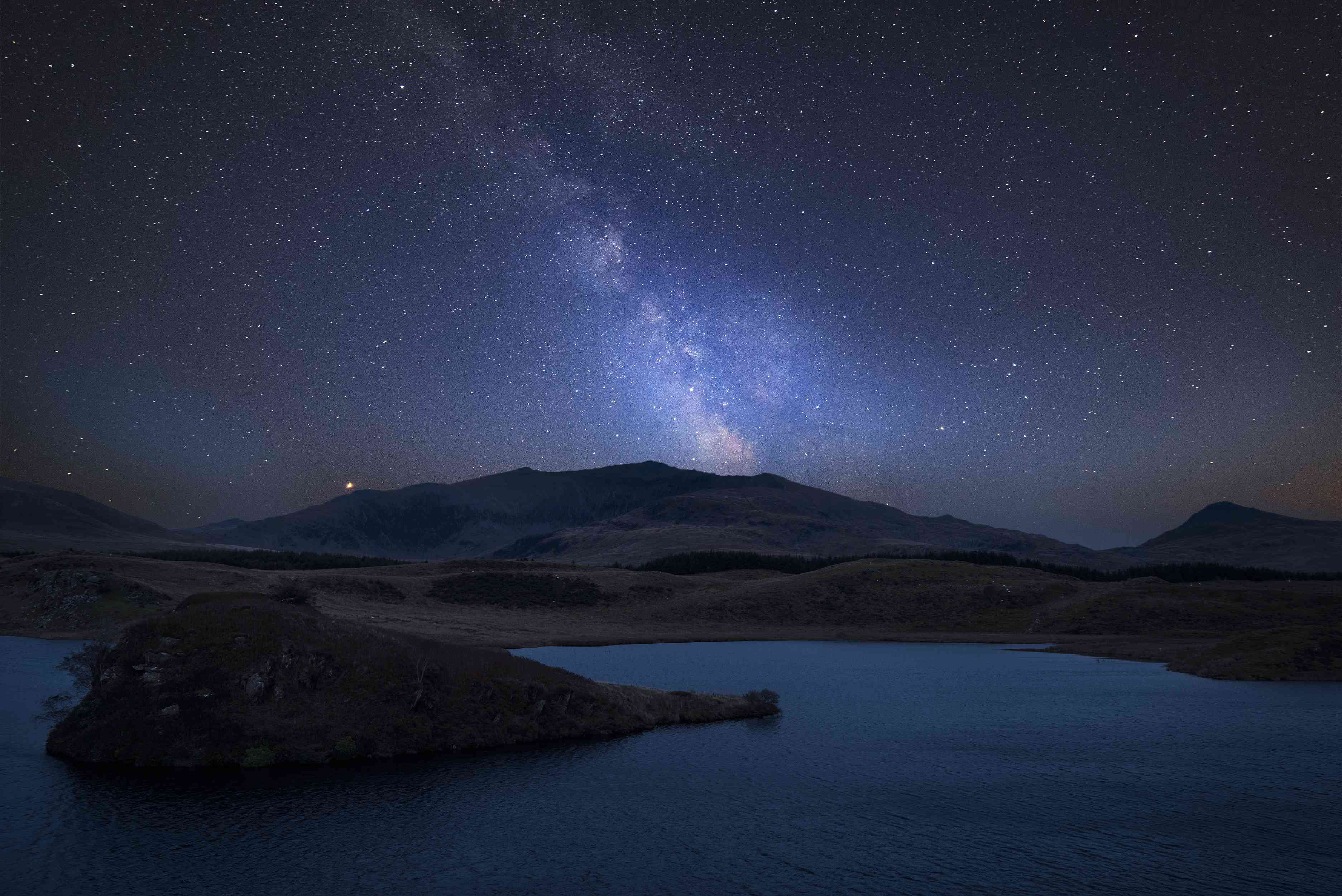 Starry sky over mountains and deep blue lake