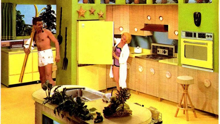 Two people standing in a large retro kitchen