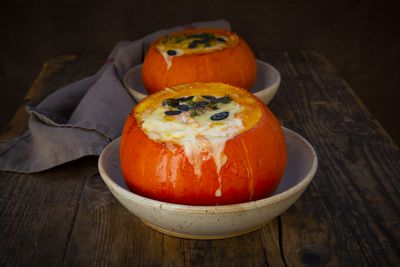 Two Hokkaido squashes stuffed with Camembert cheese, thyme and pumpkin seeds