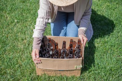 person in straw hat crouches in grass with a cardboard box of used brown glass bottles