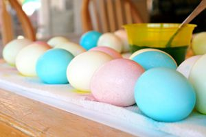 Blue, light yellow, and pale pink dyed eggs on a table