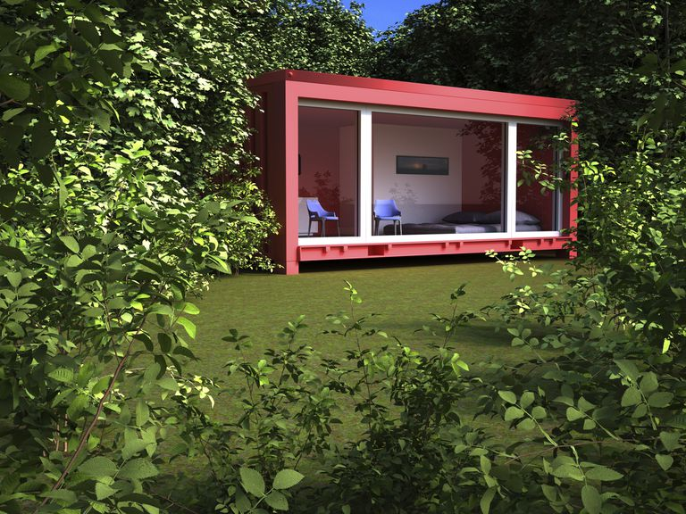 A red shipping container home in surrounded by greenery.