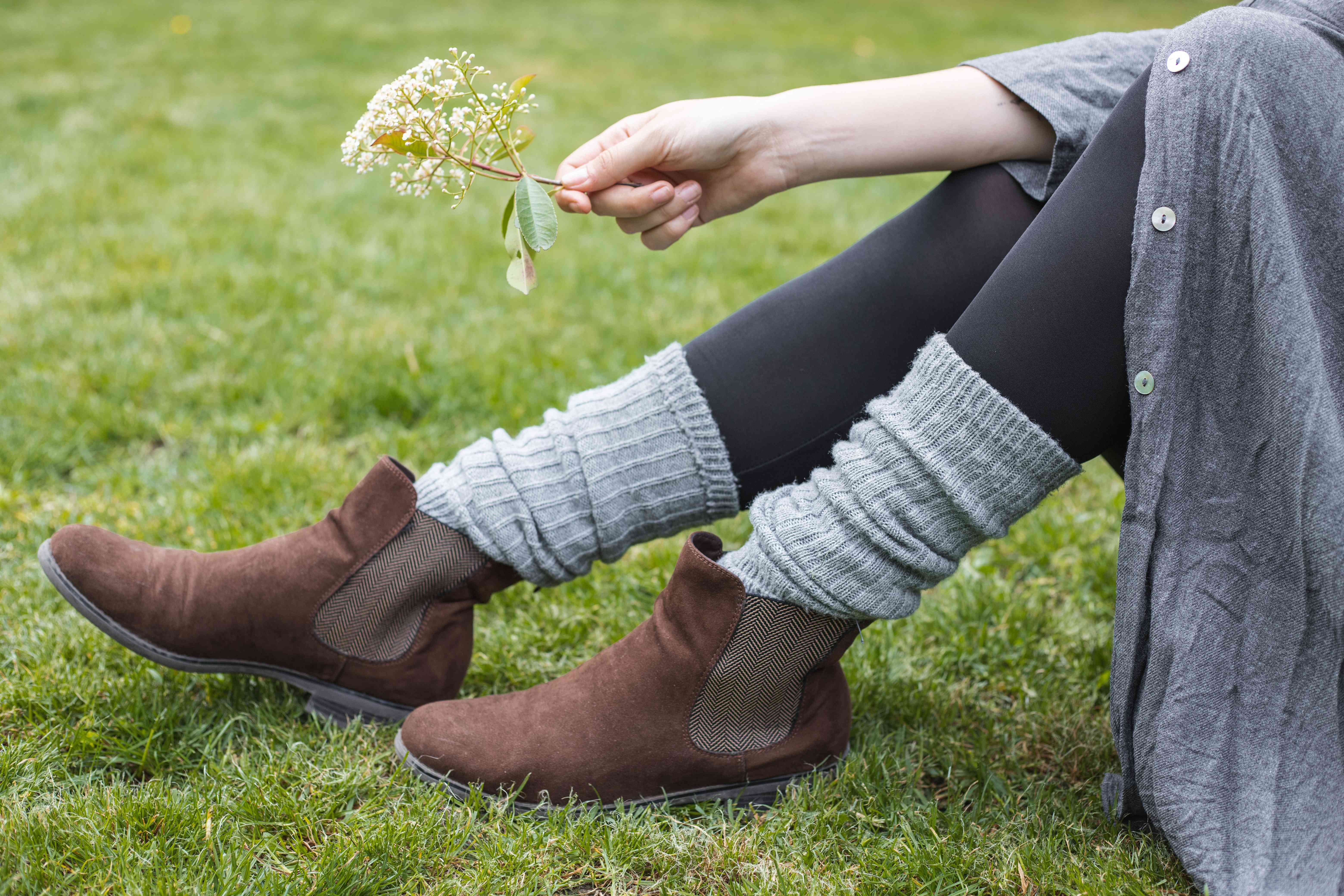 model lounges on grass wearing gray knitted boot toppers and holding sprig of flower