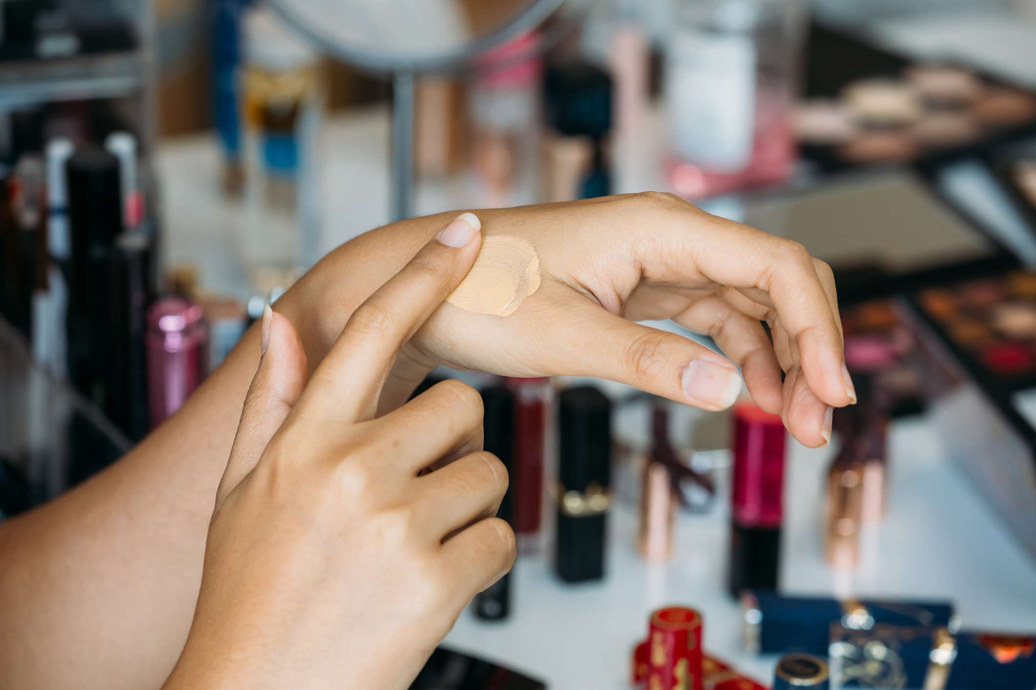 A woman applies concealer to her hand with cosmetics in the background.