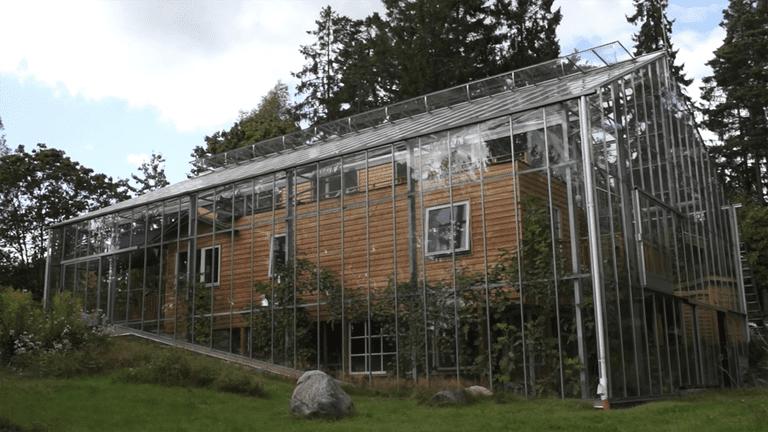 Pareja rodea una casa ecológica con un invernadero para mantenerla caliente (video)