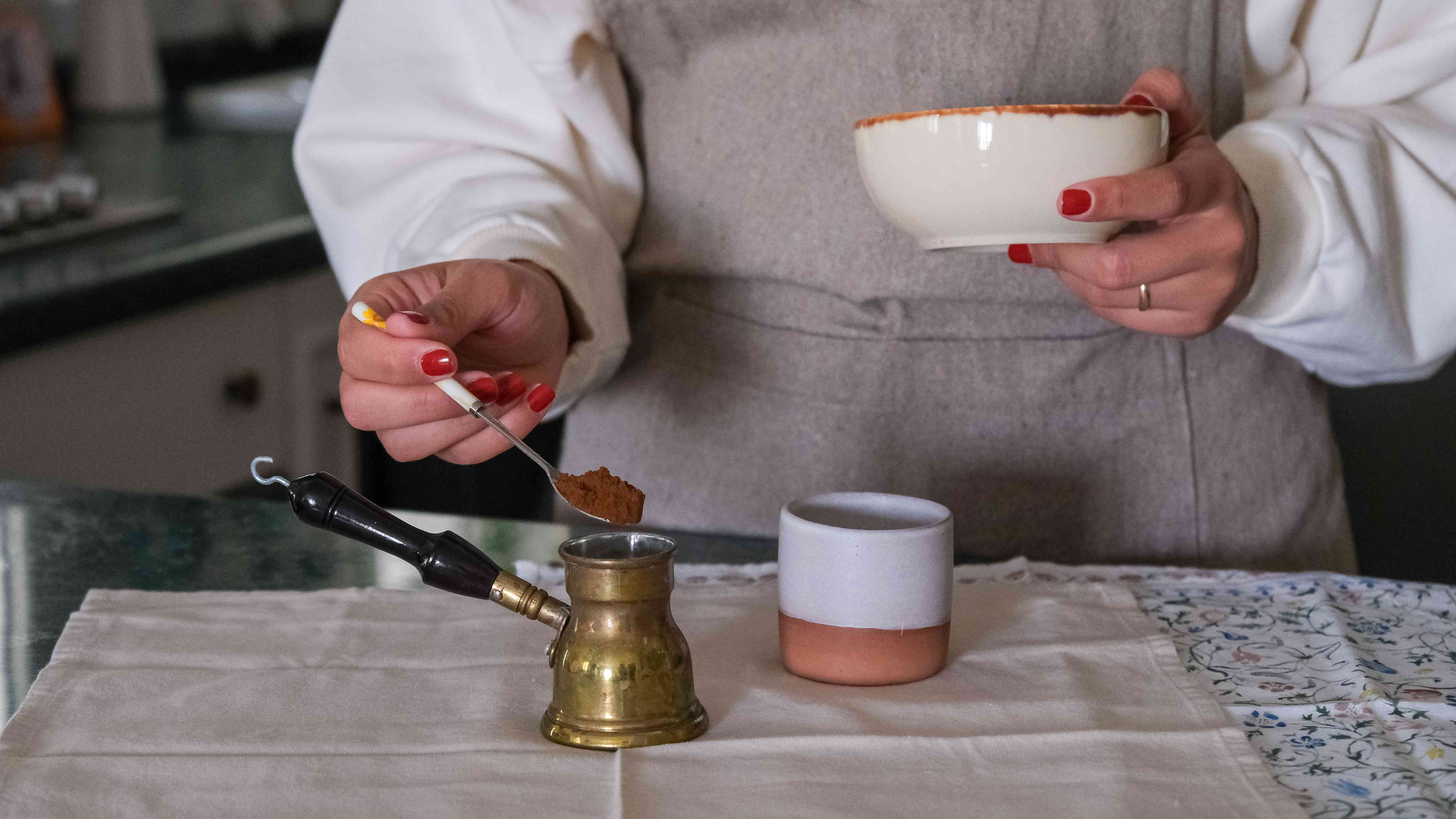 waist shot of person preparing Turkish coffee with ceramic cup and brass Turkish coffee pot