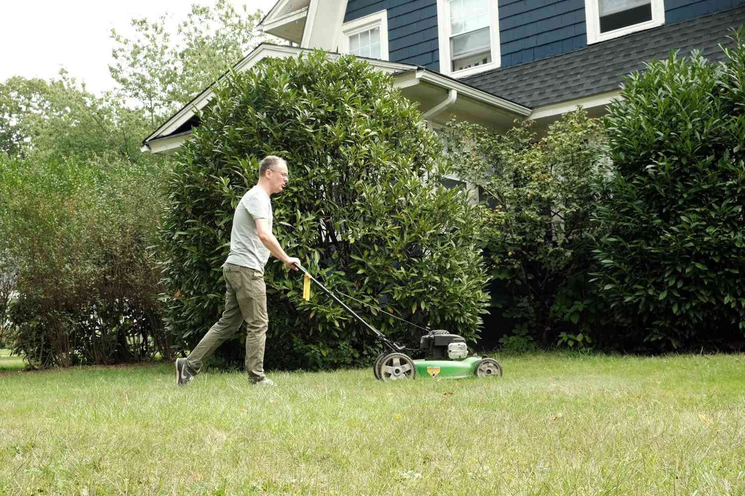 older man mows lawn with house behind