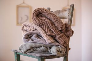 cozy chunky sweaters in earth tones are piled up on wooden chair