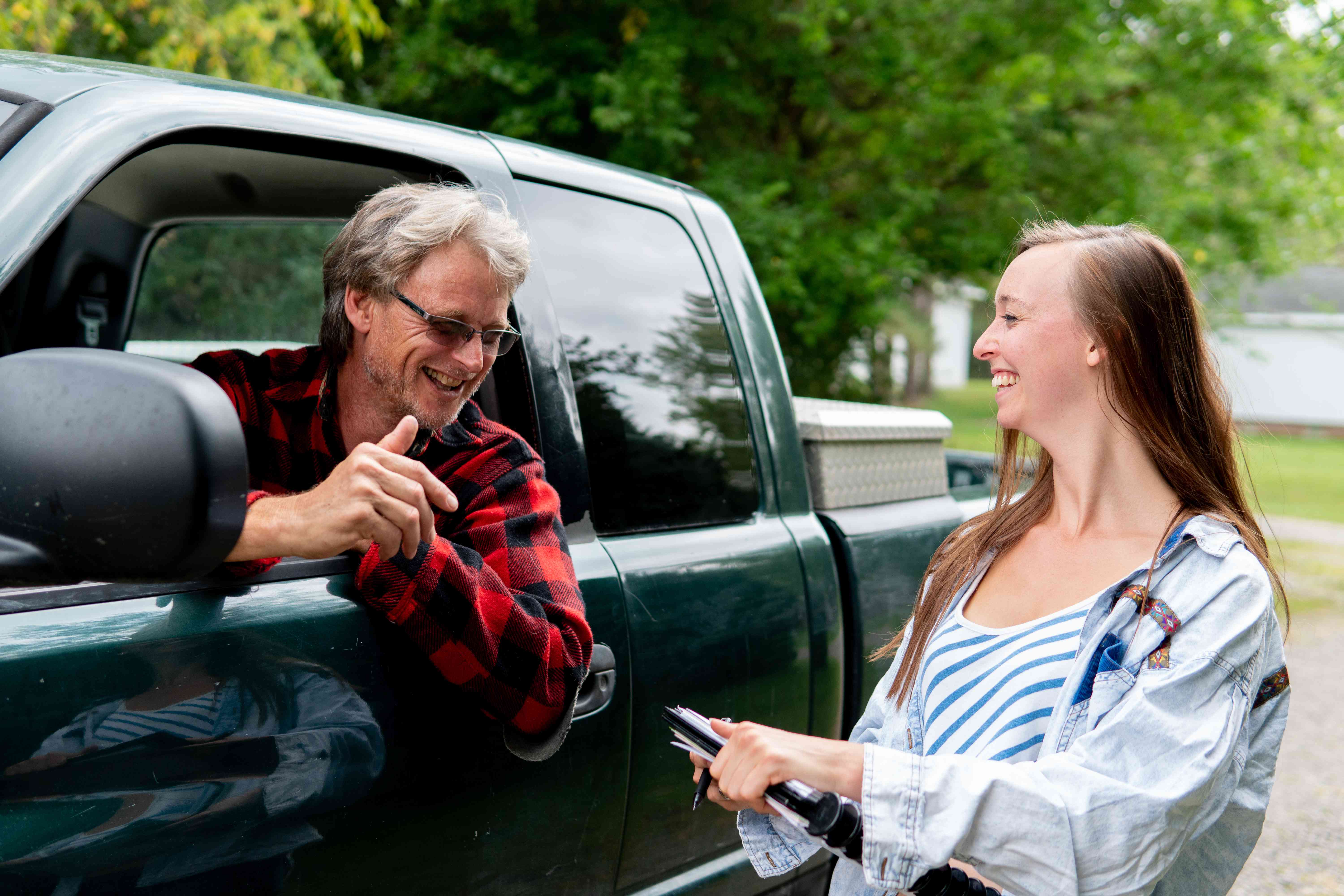 older man in truck leans out window to talk to young woman with clipboard