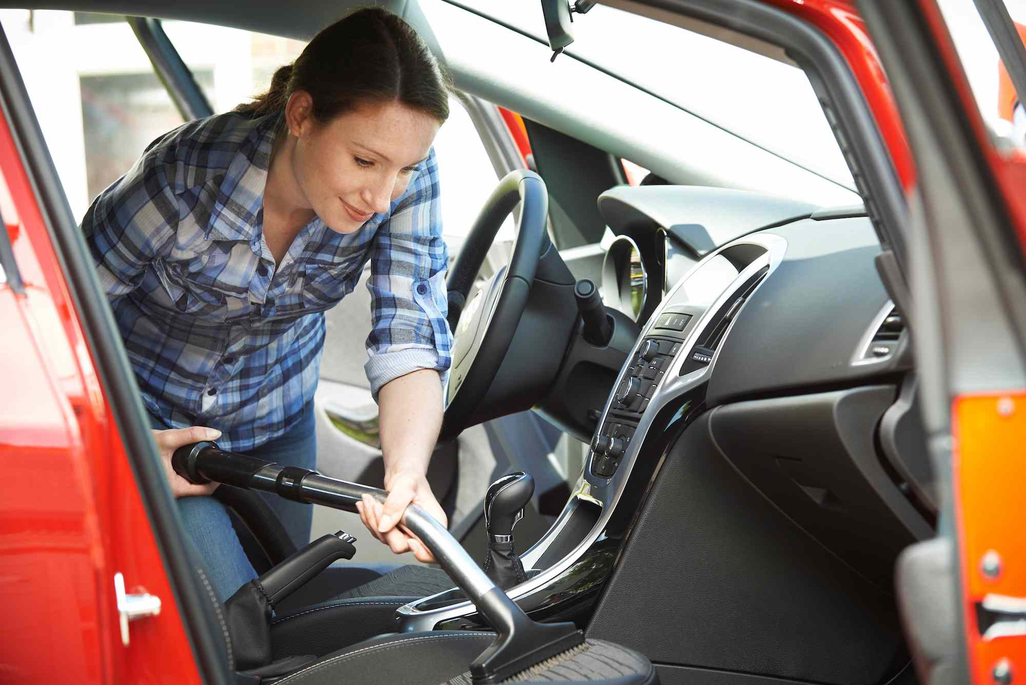 A woman cleans the interior of her car using a vacuum cleaner.