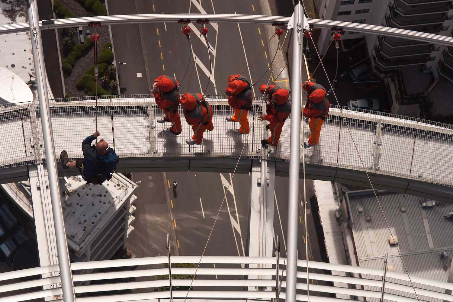 Five orange-clad visitors navigate the SkyWalk with the help of a guide.