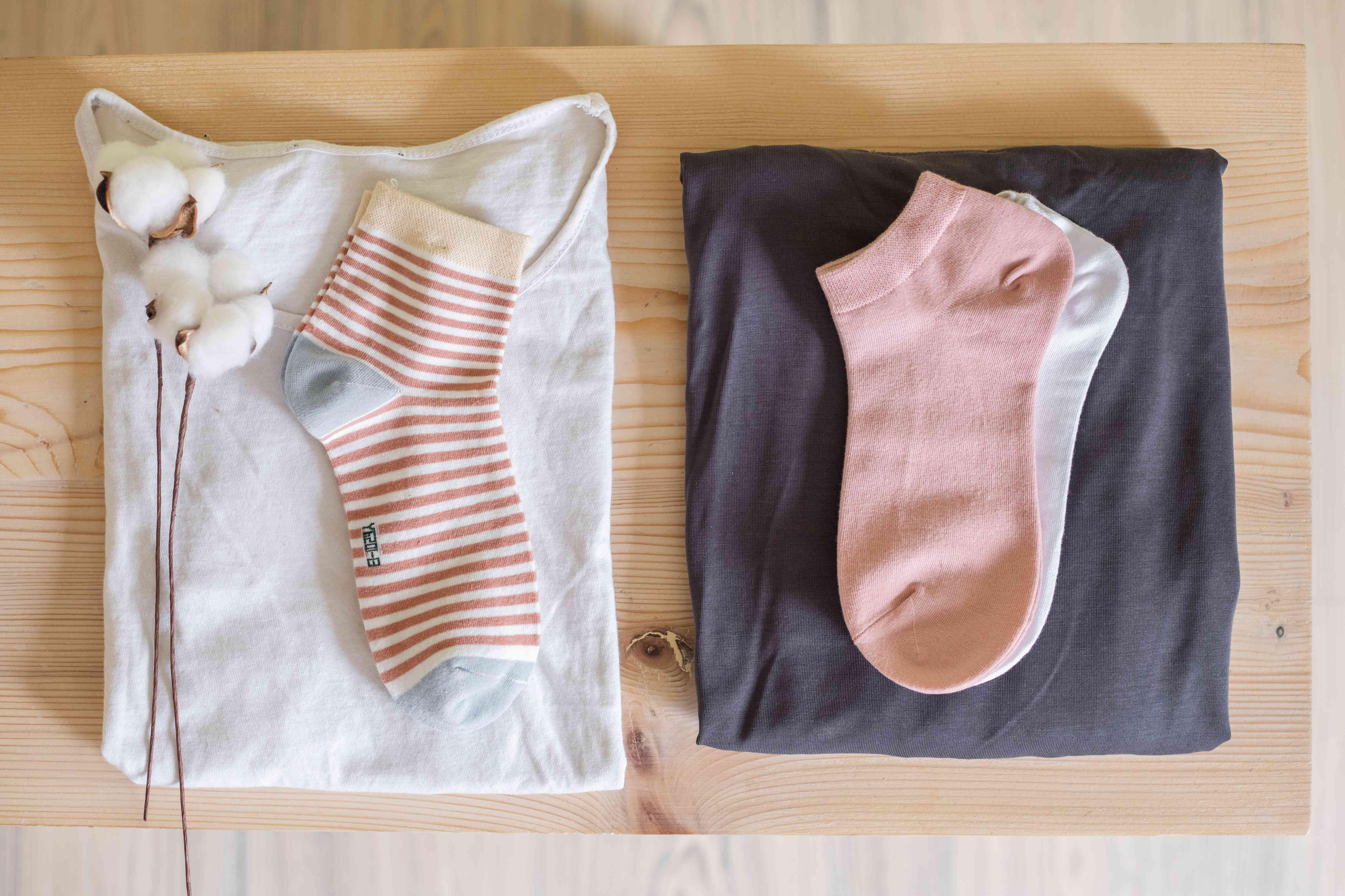 flat lay shot of cotton shirt and socks and cotton boll next to modal shirt and socks