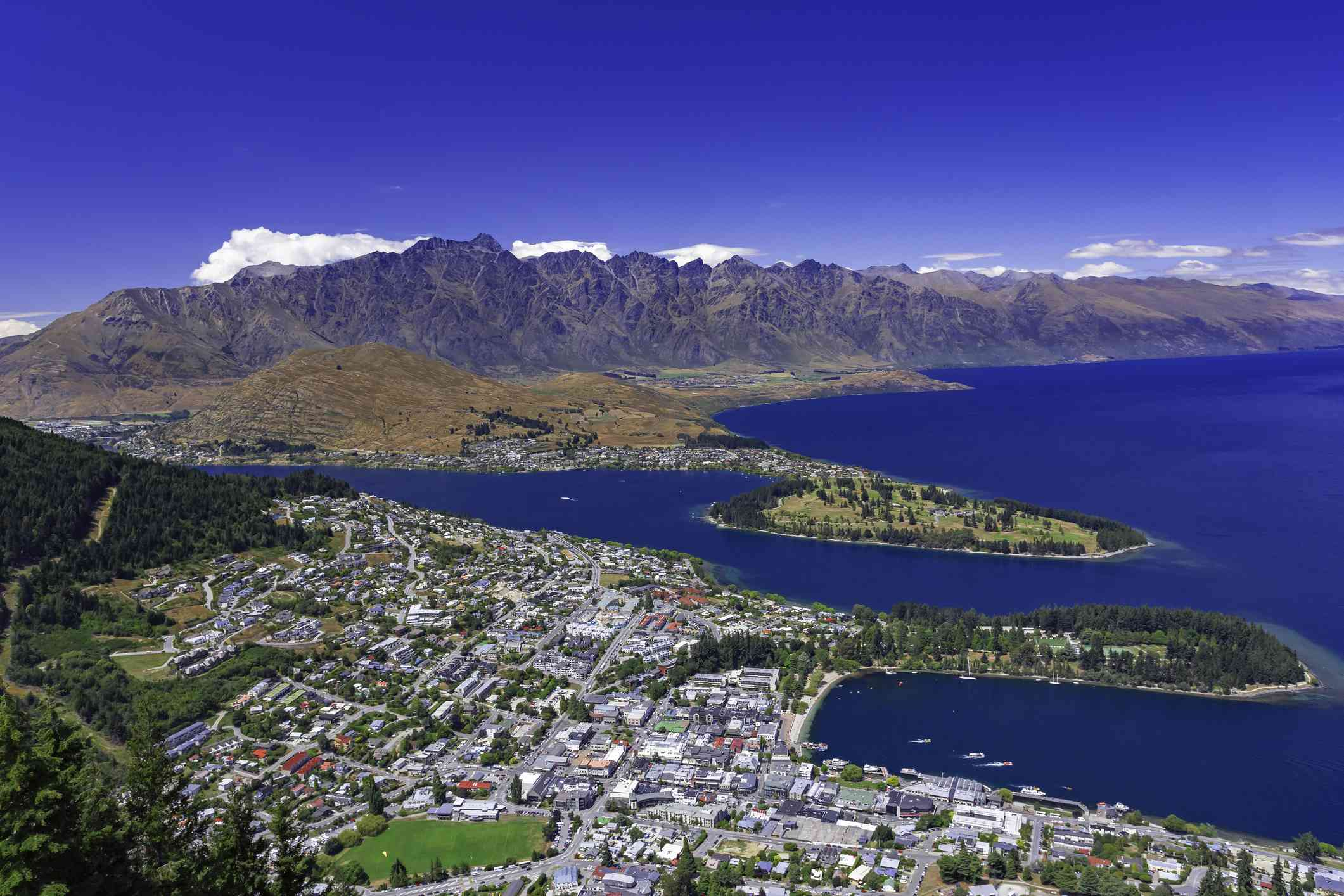 Aerial view of Queenstown from Bob's Peak with the city in the foreground next to the vivid blue water with mountain peaks in the distance below a bright blue sky