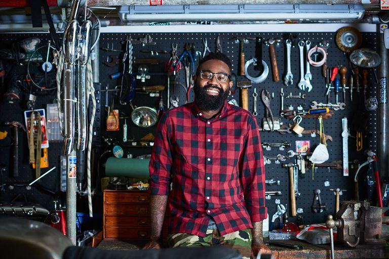 Portrait of smiling owner in motorcycle workshop with tools in background a wearing flannel shirt