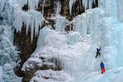 Ice climber on the frozen Upper Falls of the Johnston Creek