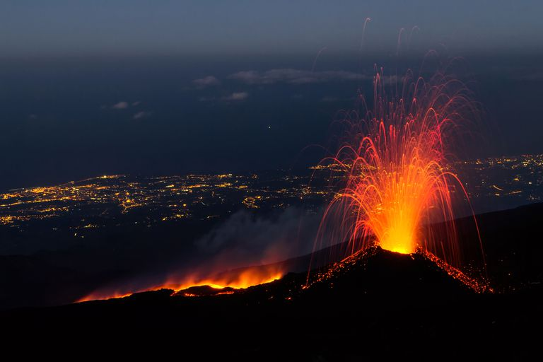 An erupting volcano near a large city